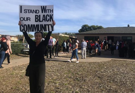 "Dania Brett, University Senate Administrative Analyst, holds a sign that says ""I stand with our black community"" outside the Black Resource Center on the afternoon of April 15, 2019."