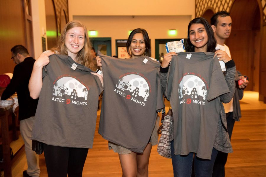 Three+students+get+free+shirts+in+Montezuma+Hall+during+one+of+the+Aztec+Nights+events+in+2017.+This+year+Aztec+Nights+events+will+also+give+away+free+items+and+food+on+campus.