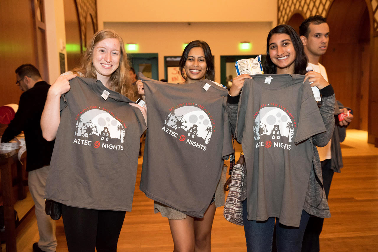Three students get free shirts in Montezuma Hall during one of the Aztec Nights events in 2017. This year Aztec Nights events will also give away free items and food on campus.