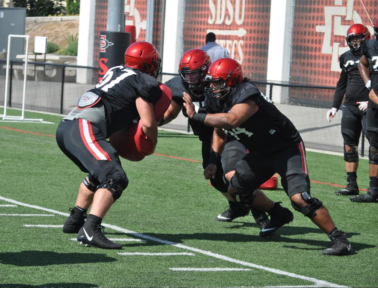 San Diego State offensive linemen work on a drill during a fall camp practice on Aug. 7 at SDSU Practice Field.