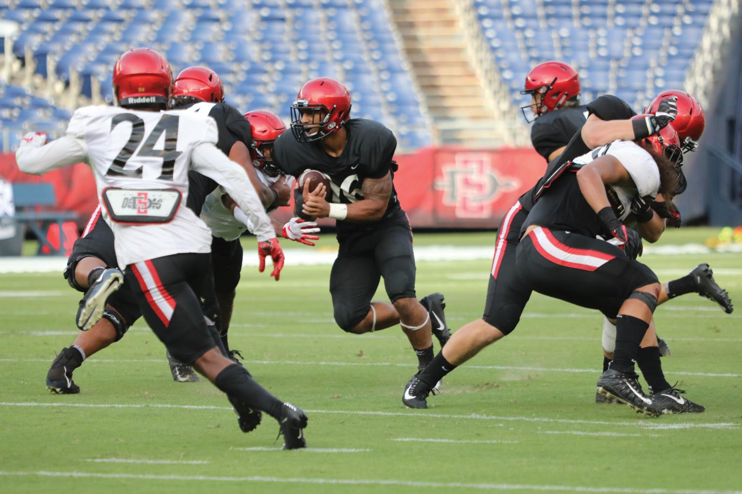 Sophomore running back Kaegun Williams runs through the defense during the Aztecs' scrimmage at the annual Fan Fest on Aug. 17 at SDCCU Stadium.