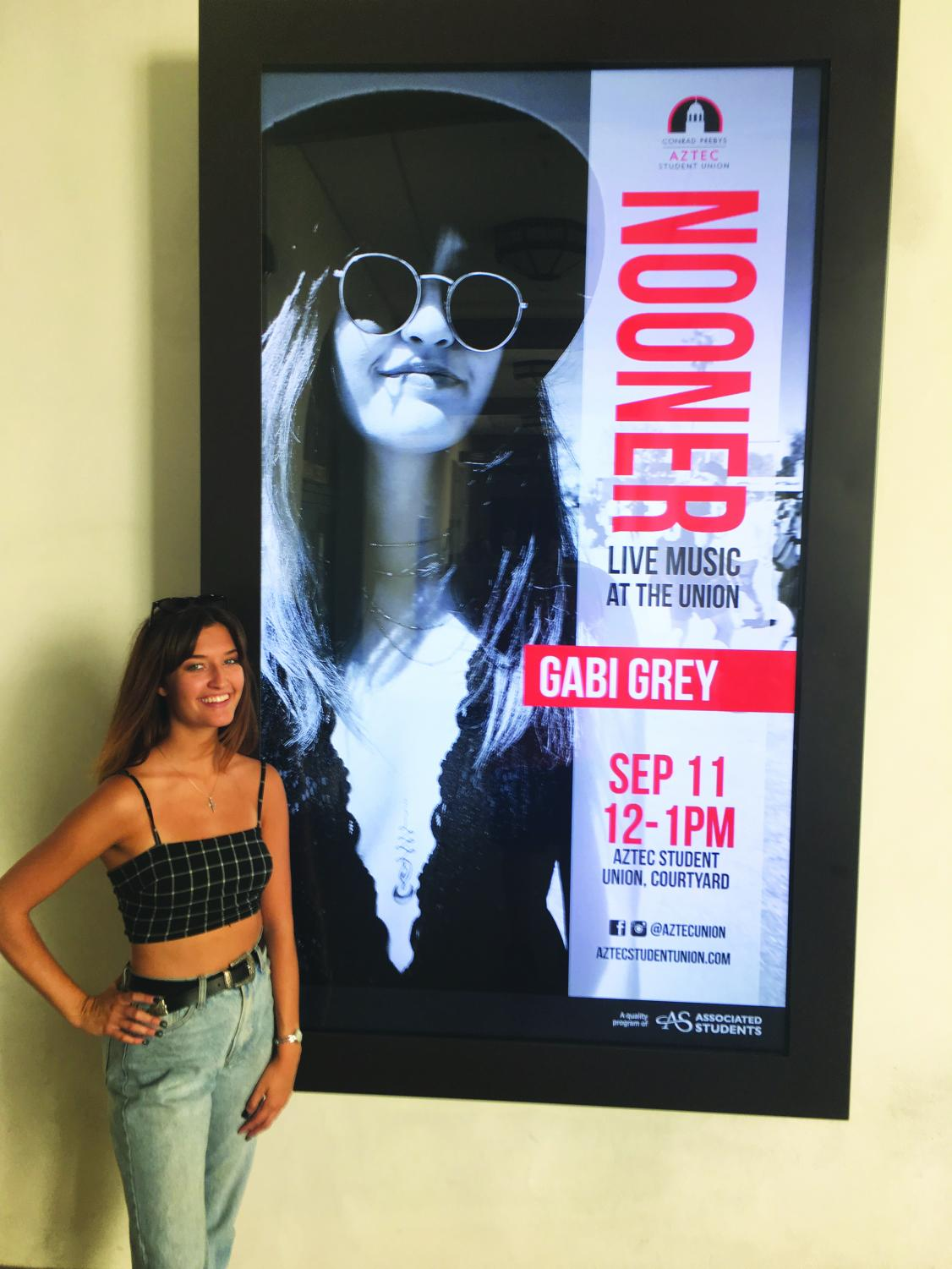 Budihas stands in front of her sign in the Aztec Student Union where she will be performing live on September 11.
