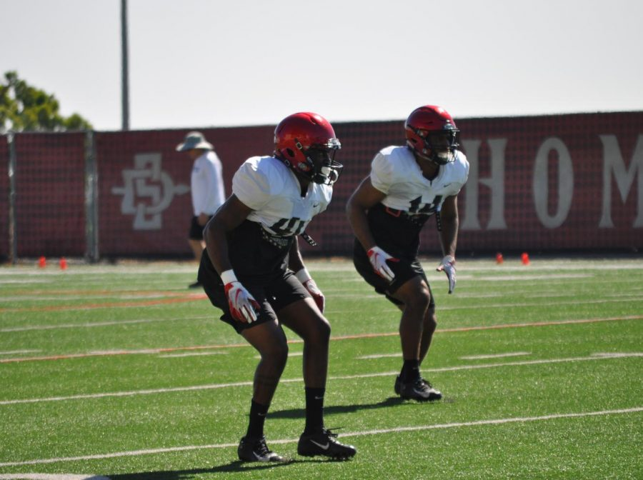 Senior cornerback Sammy Morrison (left) and junior safety Tariq Thompson (right) drop back in coverage during a fall practice at the SDSU Practice Field.
