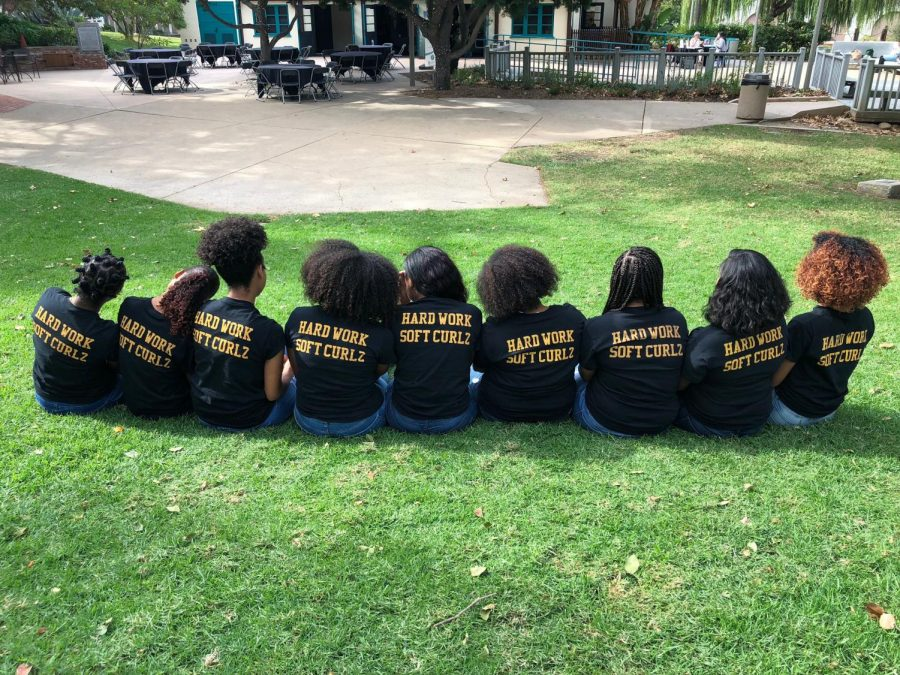 Members of the SDSU chapter of Campus Curlz sat on the grass by the turtle pond on campus with their matching shirts with the slogan,