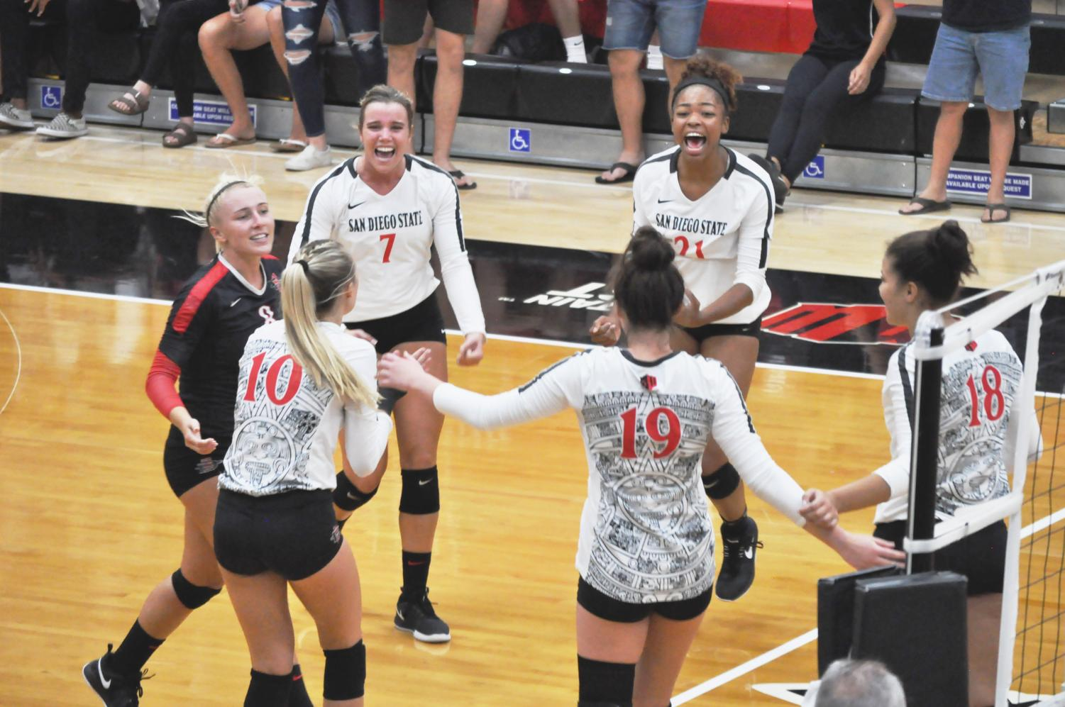Senior outside hitter Hannah Turnlund (7) and sophomore outside hitter (21) celebrate an Aztec point during the Aztecs' 3-2 comeback victory over West Virginia on Sept. 6 at Peterson Gym.