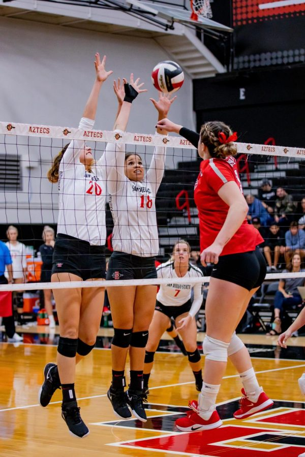 Junior outside hitter Lexie Hamrick (20) and senior middle blocker Tamia Reeves (18) attempt to block an attack from a UNLV player during the Aztecs' 3-1 loss to the Rebels on Oct. 3 at Peterson Gym.