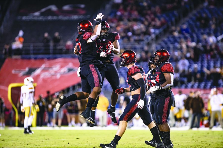 Sophomore defensive lineman Keshawn Banks (left) and senior defensive lineman Myles Cheatum (right) celebrate in the air during the Aztecs' 26-22 win against Wyoming on Oct. 12 at SDCCU Stadium.