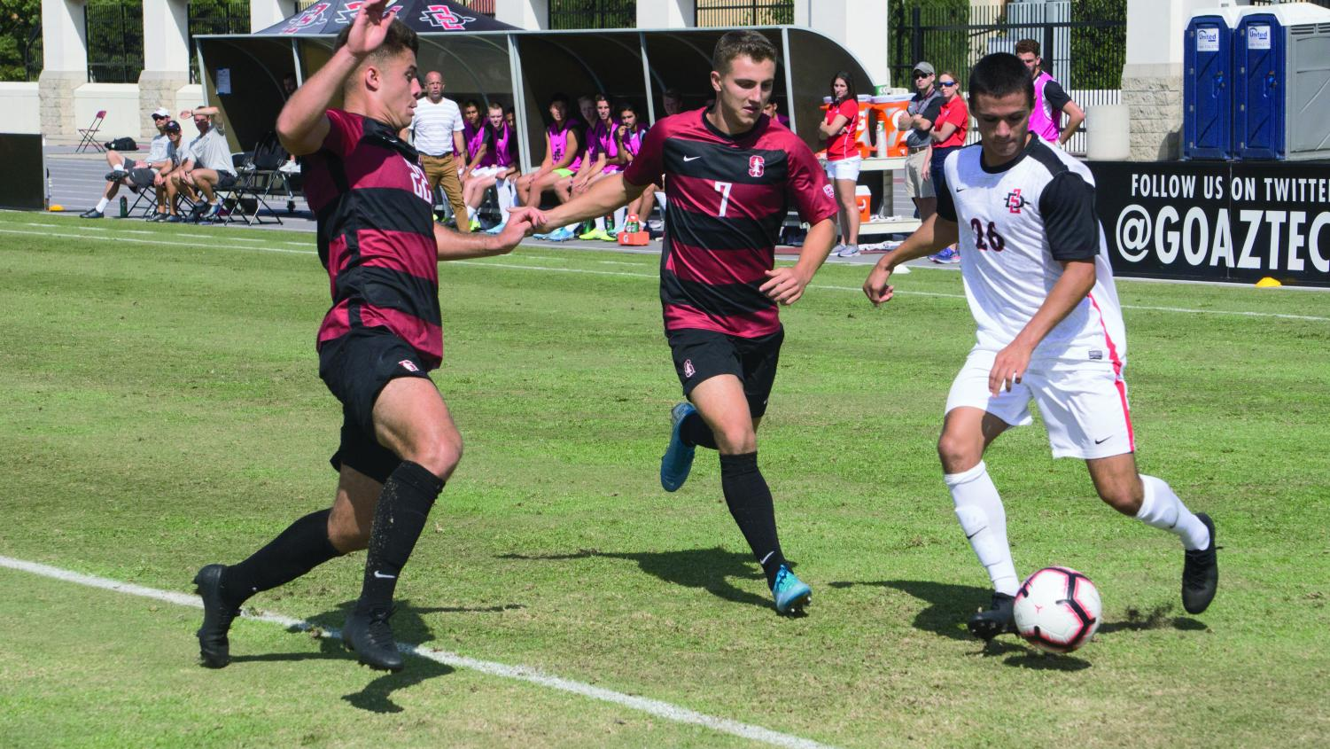 Freshman midfielder Blake Bowen attempts to get past two Stanford defenders during the Aztecs' 1-0 loss to the Cardinal on Oct. 13 at the SDSU Sports Deck.