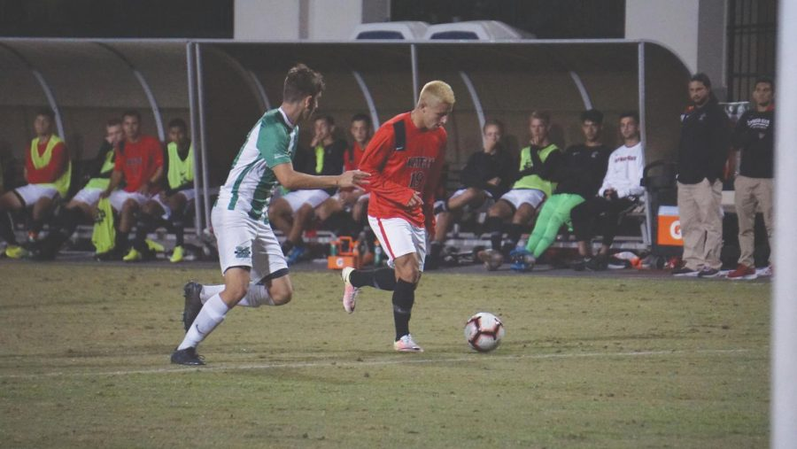 Sophomore midfielder Tristan Weber (19) attempts to dribble the ball past the Marshall defender during the Aztecs' 5-1 loss to Marshall on Oct. 18 at the SDSU Sports Deck.