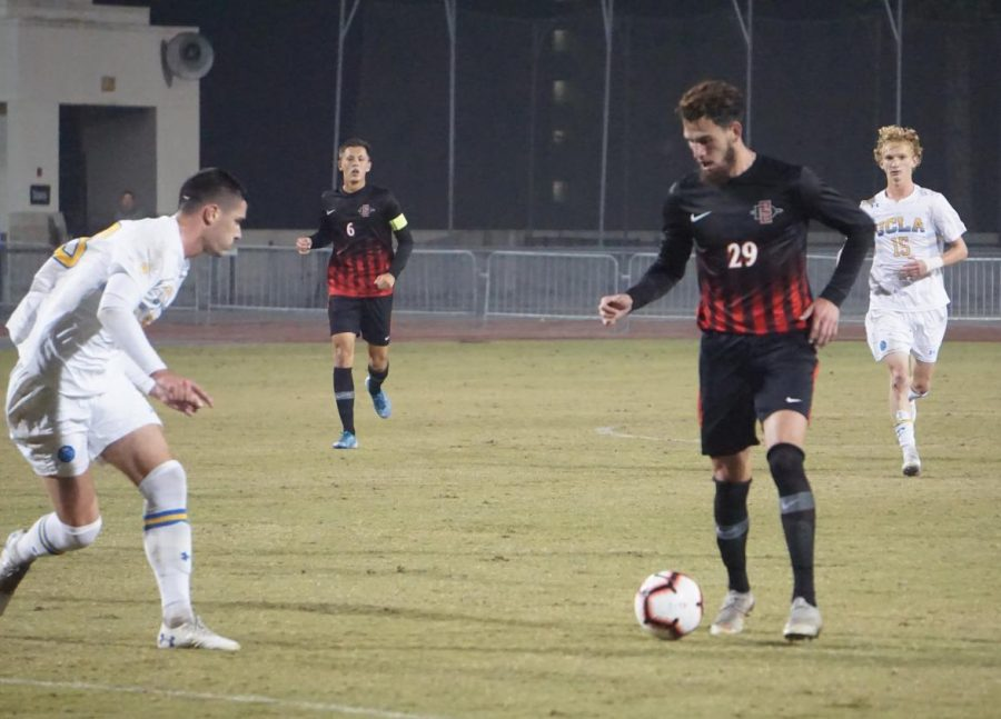 Senior midfielder Adam Vargas attempts to get past a UCLA defender in the Aztecs' 1-0 loss to the Bruins on Nov. 16 at the SDSU Sports Deck.