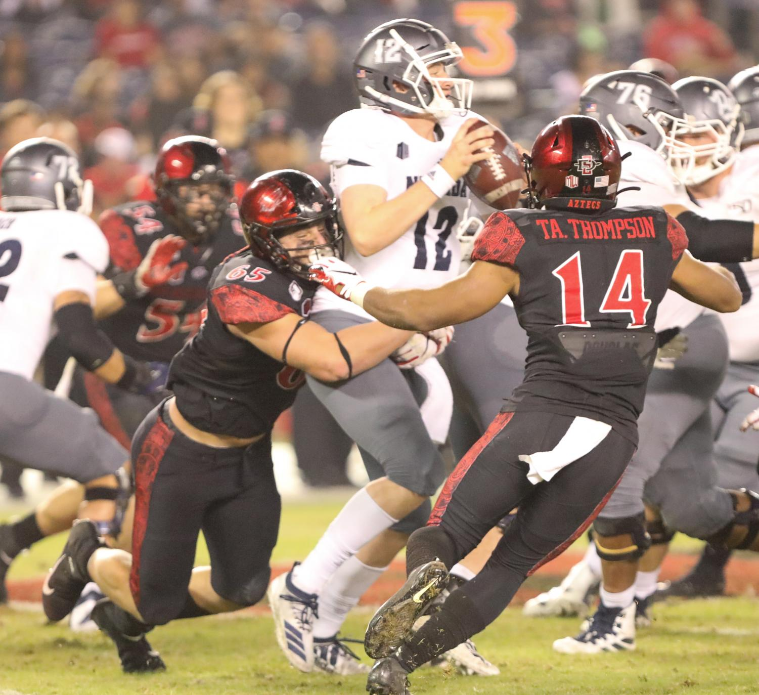 Redshirt freshman defensive lineman (65) takes down Nevada redshirt freshman quarterback Carson Strong during the Aztecs' 17-13 loss to the Wolf Pack on Nov. 9 at SDCCU Stadium.