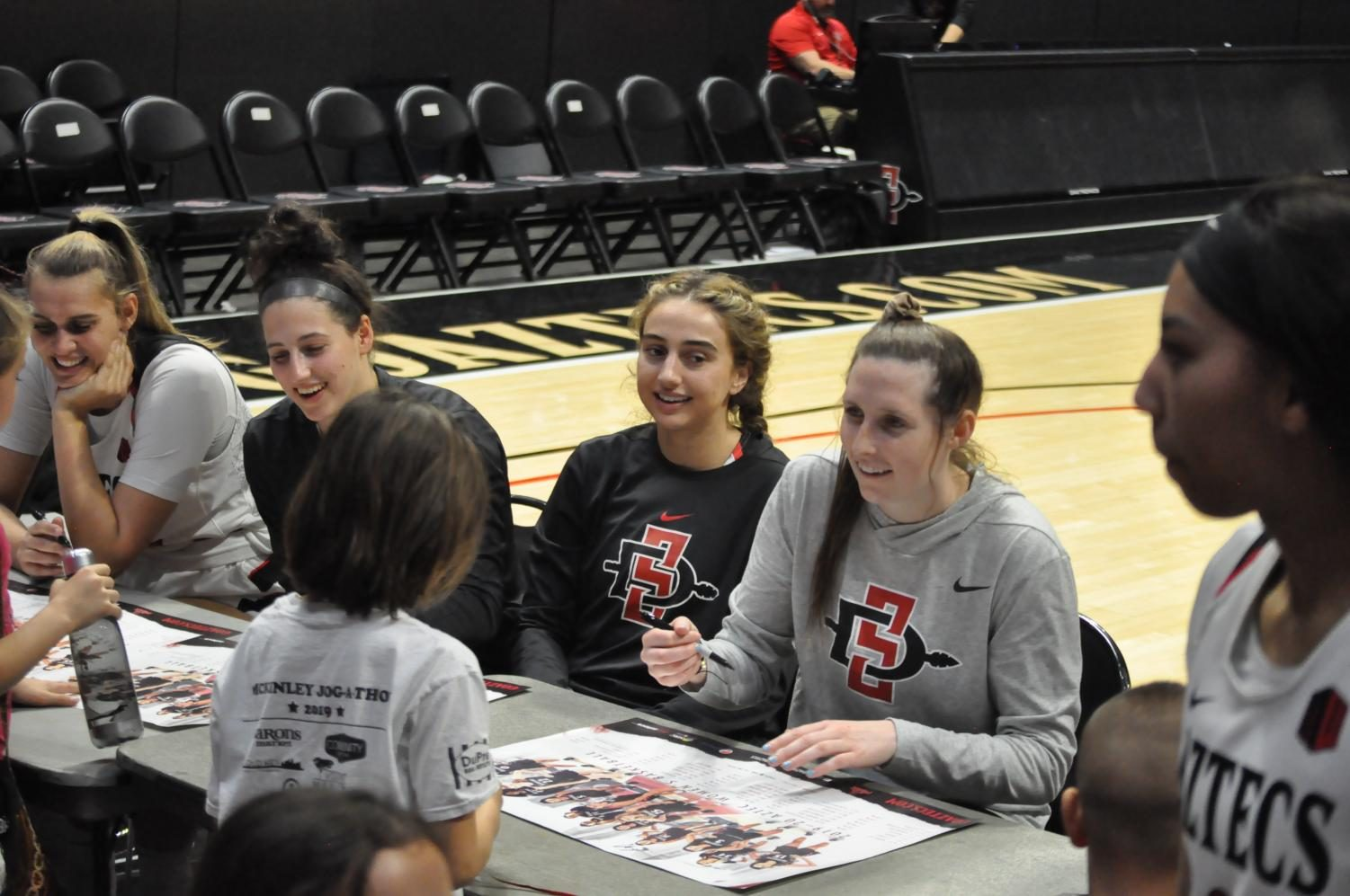 Members of the Aztecs women's basketball team  sign autographs following their matchup against Air Force on Saturday.