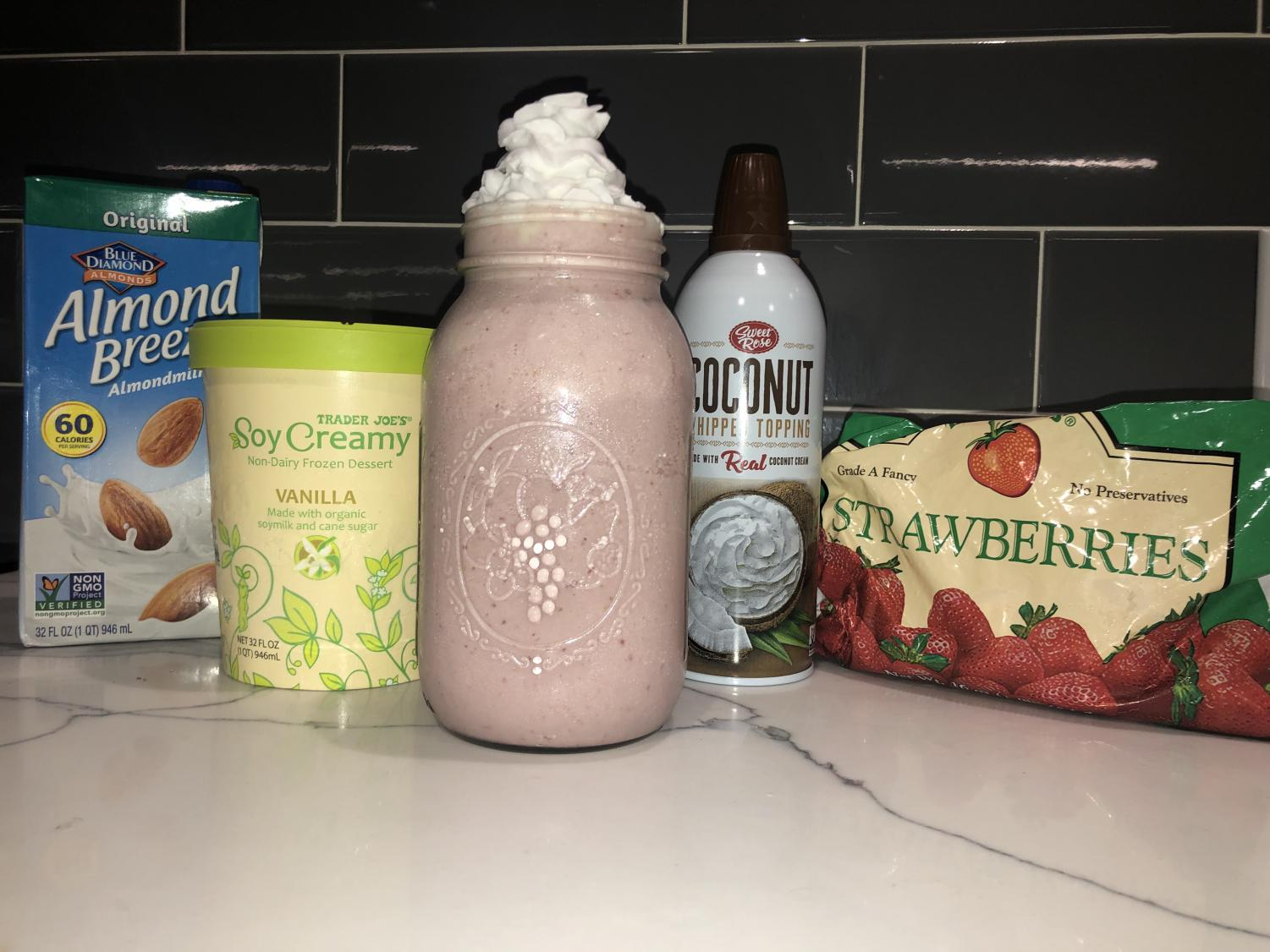 The ingredients and final product for the vegan strawberry milkshake.