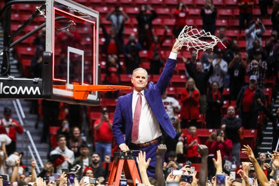 Aztecs head coach Brian Dutcher cuts the nets after defeating New Mexico for the Mountain West regular-season title on Feb. 11 at Viejas Arena.