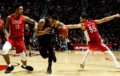 Junior guard Matt Mitchell attempts to secure the ball away from the UNLV defender during SDSU's 66-63 loss against UNLV on Feb. 22 at Viejas Arena.