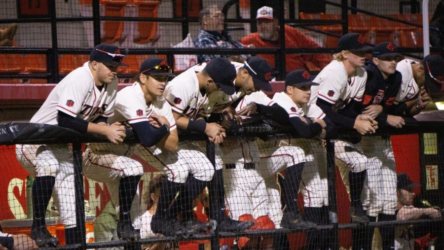 San Diego State baseball players look towards the field from the dugout during the Aztecs' 4-1 win over Iowa on Feb. 21, 2020 at Tony Gwynn Stadium.