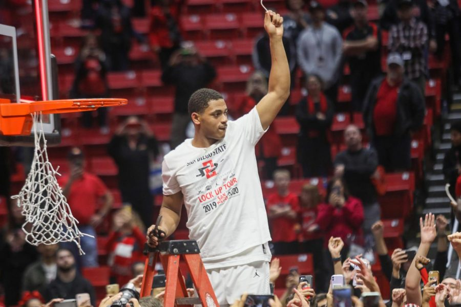 Then-junior forward Matt Mitchell holds up a piece of the net after the Aztecs defeated New Mexico 82-59 on Feb. 11, claiming the Mountain West regular-season title at Viejas Arena.