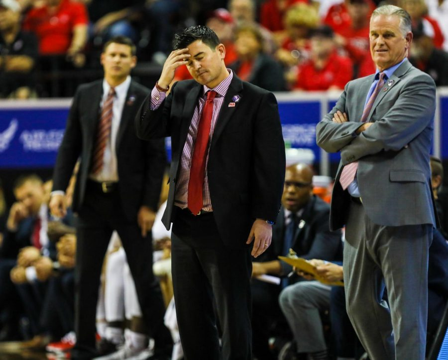 Aztecs assistant coach David Velasquez (middle) puts his head down in disappointment during the Aztecs' 59-56 loss to Utah State on March 11 at the Thomas and Mack Center.