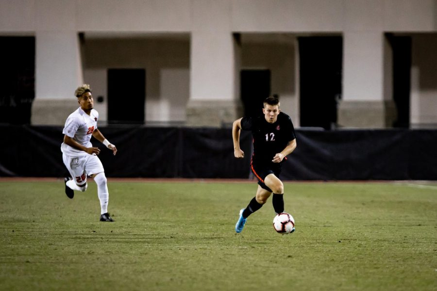 Then-freshman forward Hunter George dribbles the ball while being pursued by an Oregon State player during the Aztecs' 1-0 overtime loss to the Beavers on Oct. 24, 2019 at the SDSU Sports Deck.