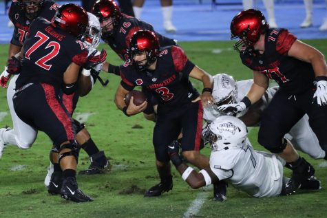 Sophomore quarterback Carson Baker attempts to escape a defender during the Aztecs