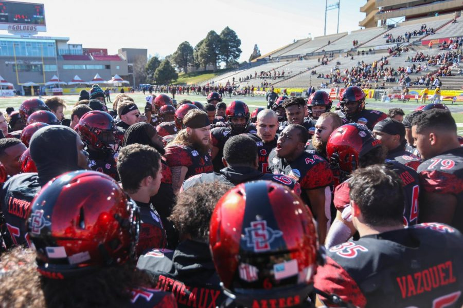 The San Diego State football team huddles around then-senior linebacker Kyahva Tezino as he gives a pregame speech. The game resulted in a 48-11 win over Central Michigan on Dec. 21, 2019 at the New Mexico Bowl in Albuquerque.