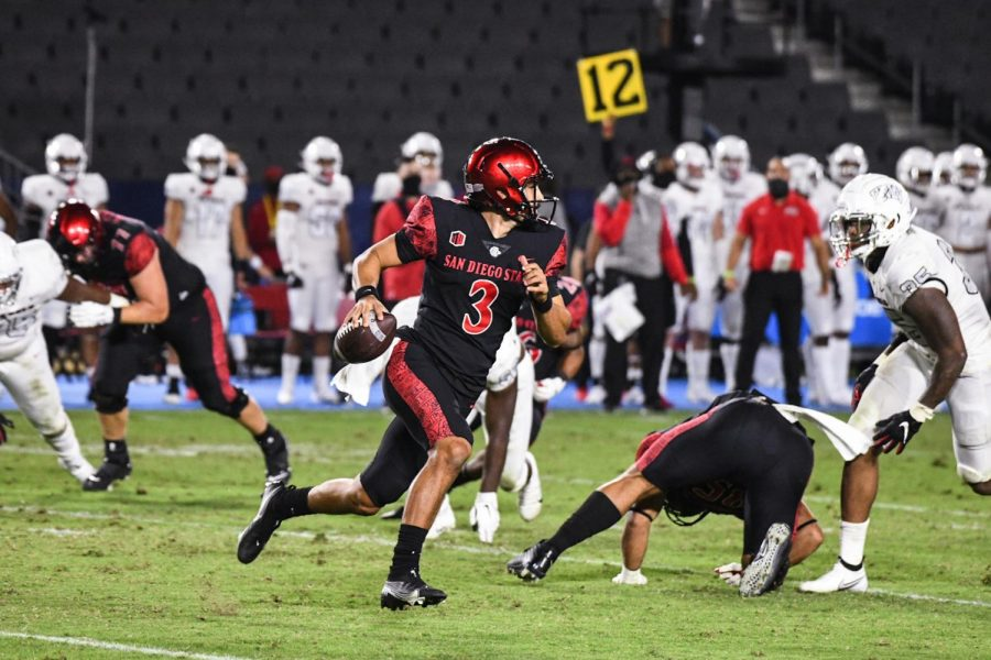 Sophomore quarterback Carson Baker scrambles away from UNLV defenders during the Aztecs' 34-6 win over the Runnin' Rebels on Oct. 24 at Dignity Health Sports Park in Carson, Calif.