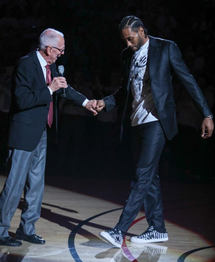 Former San Diego State men's basketball head coach Steve Fisher greets Kawhi Leonard (right) with a fist bump during Leonard's jersey retirement on Feb. 1 at Viejas Arena. The ceremony occurred at halftime of the Aztecs' 80-68 win over Utah State.