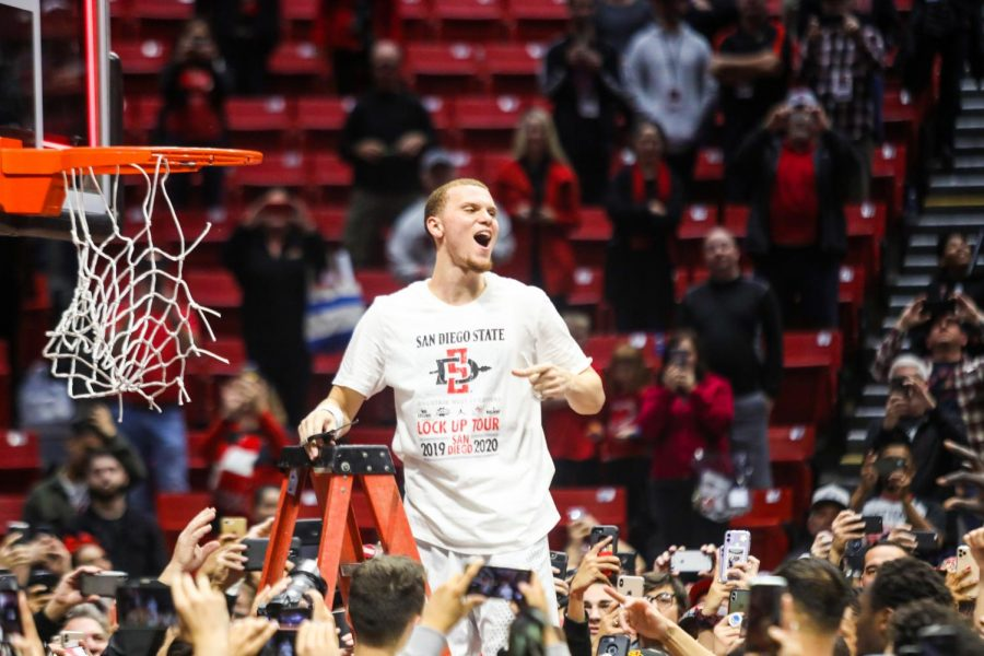 Then-junior guard Malachi Flynn celebrates after cutting down a piece of the hoop following the Aztecs' 82-59 win over New Mexico on Feb. 11. The win culminated in the Aztecs claiming the Mountain West Conference regular season title.