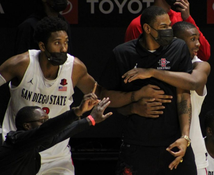The San Diego State men's basketball team celebrates after a play during the Aztecs' 69-67 win over Nevada on Jan. 9 at Viejas Arena. Senior forward Joshua Tomaić (left) looks on with freshman guard Lamont Butler, while he celebrates with his arms around sophomore forward Keshad Johnson.