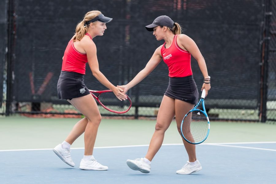 San Diego State womens tennis junior Alicia Melosch (left) high fives senior Tamara Arnold during the Aztecs 4-0 win over Air Force on April 11, 2021 at the Aztec Tennis Center.