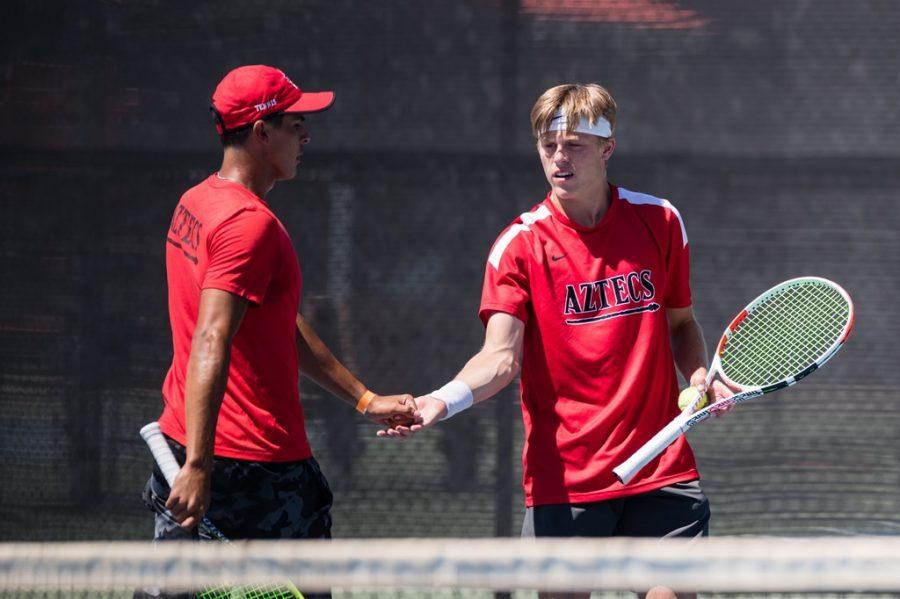 San Diego State mens tennis senior Ignacio Martinez (left) high-fives freshman Judson Blair during the Aztecs' 4-2 loss to Santa Clara on April 19, 2021 at the Aztec Tennis Center.