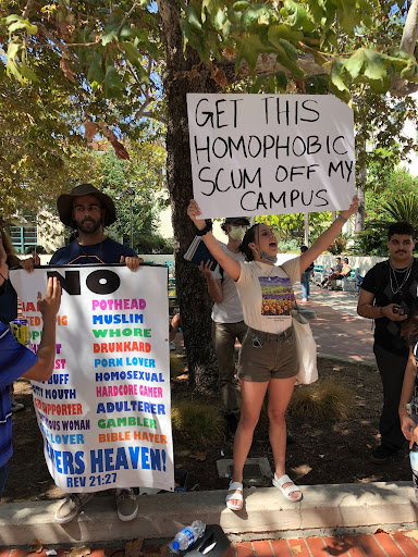 """Student holds sign that reads """"Get this homophobic scum off my campus."""""""