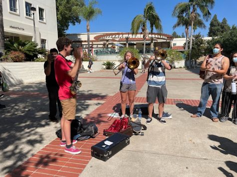 Students play trombones in an attempt to drown out the words of man spewing hate speech.