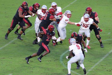Greg Bell, número 22, corre la pelota entre medio de la defensa del los Lobos para notar su touchdown.