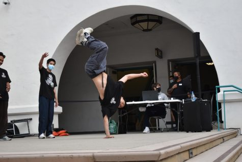 Performer Jason Hwang balancing his body using his left hand in the middle of a power move during his routine.