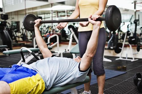 A spotter ensures a weight lifter doesn't injure himself while training. This is one of the many roles athletic trainers take on in the exercise and nutritional sciences.dept. Thinkstock