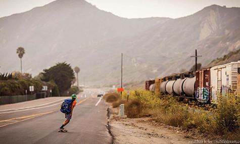 Jin Salamck skateboards the coast of California past a train.
