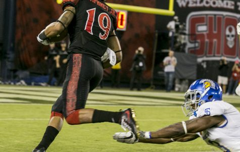 Senior running back Donnel Pumphrey (19) flies by a diving SJSU defender, on his way to a rushing touchdown.