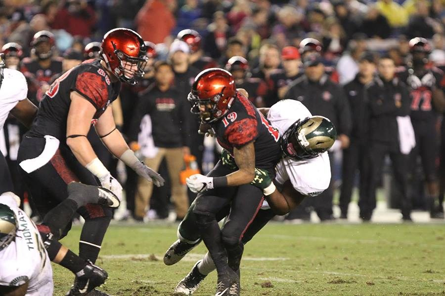 Senior running back Donnel Pumphrey (19) is tackled in the backfield by a Colorado State defender.