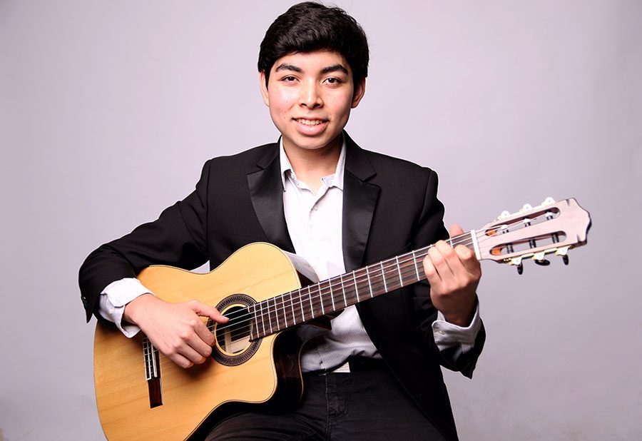 Jesus Contreras smiles with guitar.
