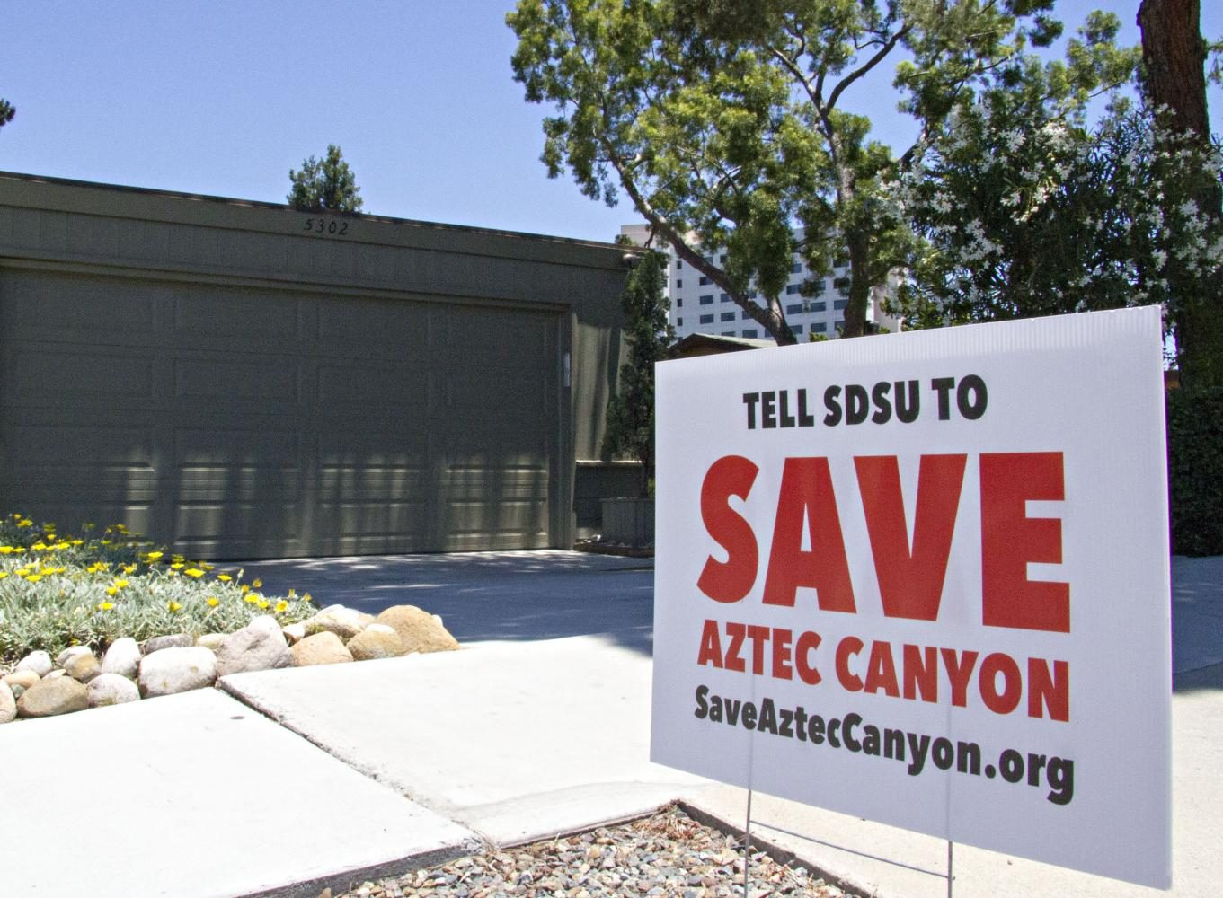 A+yard+sign+reading+%22Tell+SDSU+to+save+Aztec+Canyon%22+sits+in+front+of+a+green+house.+Chapultapec+Hall+is+visible+in+the+background.
