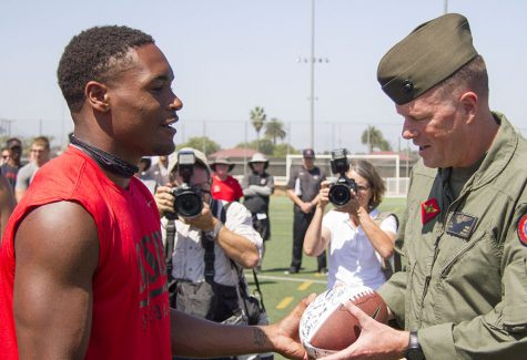 Senior cornerback Kameron Kelly presenting a signed football to Major General Mark Wise.