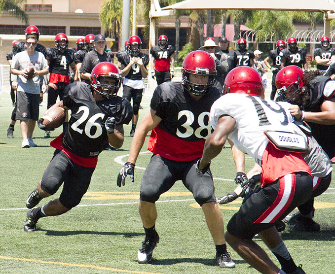 SDSU freshman fullback Adam Eastwood blocks for freshmen running back Kaegun Williams during the team's practice at Miramar MCAS.