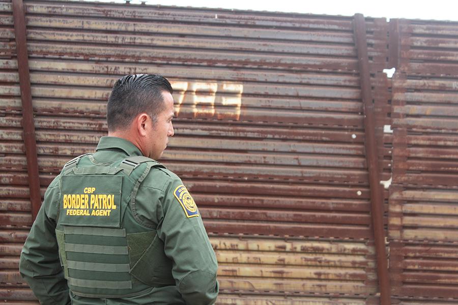 Agente de la patrulla fronteriza de San Diego Saul Rocha ve hacia la cerca.