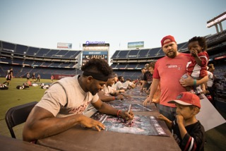 SDSU senior running back Rashaad Penny autographing a young fans football poster at Fan Fest.