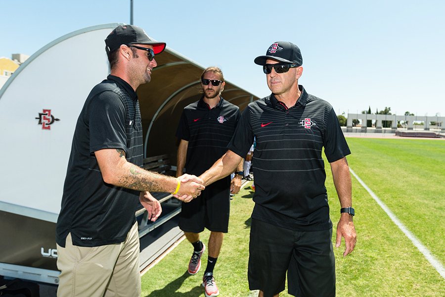 SDSU head coach Mike Friesen shakes hands with an assistant coach.