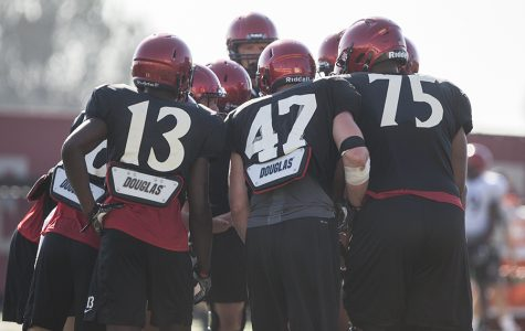 SDSU football players huddle during practice on Aug. 10, 2017.