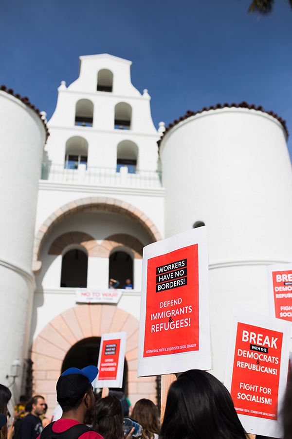 Protesters hold signs advocating for the International Youth and Students for Social Equality during a February protest in front of Hepner Hall.