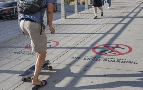 A skateboarder rides on a footbridge where it is not allowed.