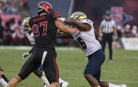 Sophomore tight end Kahale Warring blocks a UC Davis defender.